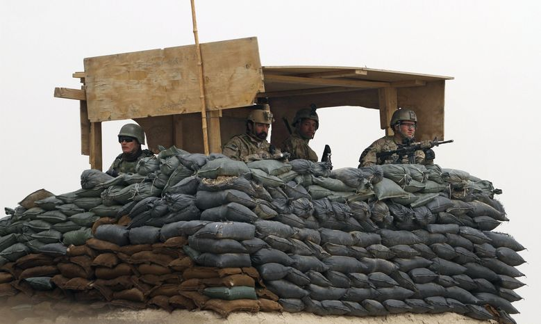 U.S. Army and Afghan troops stand watch in a guard tower at their base in Panjwai, Afghanistan, in Kandahar province, on Sunday, March 11, 2012, after a U.S. Army sergeant allegedly killed 16 Afghan civilians in nearby villages. (AP Photo/Allauddin Khan)