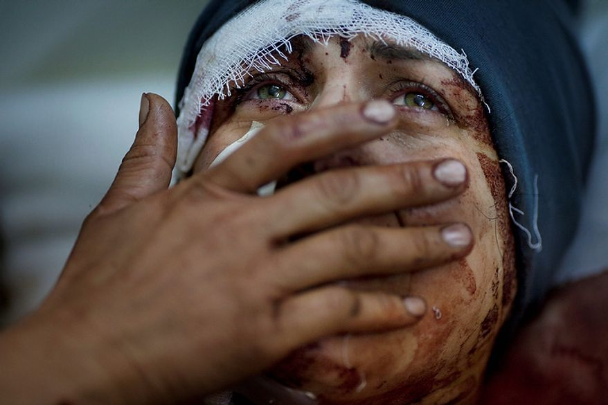 In this photo from March 10, 2012, Aida cries as she recovers from severe injuries after the Syrian Army shelled her house in Idlib north Syria. Aida's husband and and two children were killed after their home was shelled. (Associated Press)