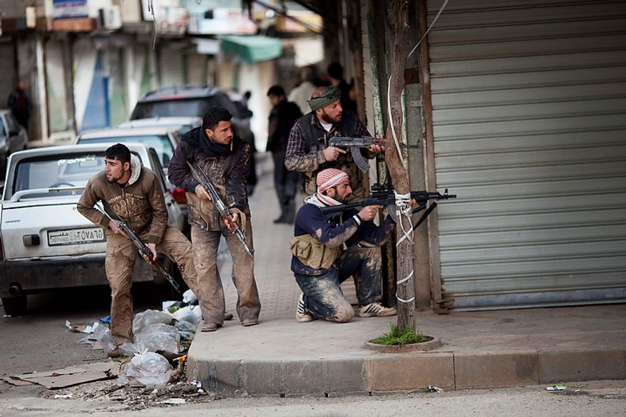 In this photo from March 11, 2012, Syrian rebels take position during clashes with government forces in Idlib, north Syria. Syrian activists said that pro-government gunmen have killed several people including children in a rebel stronghold recaptured by the government in the embattled central city of Homs. (Associated Press)