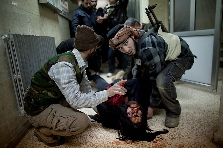 In this photo from March 11, 2012, Syrian rebels carry the dead body of a comrade to a morgue after heavy fighting with Syrian government forces in Idlib, north Syria. Syrian activists said that pro-government gunmen have killed several people including children in a rebel stronghold recaptured by the government in the embattled central city of Homs. (Associated Press)