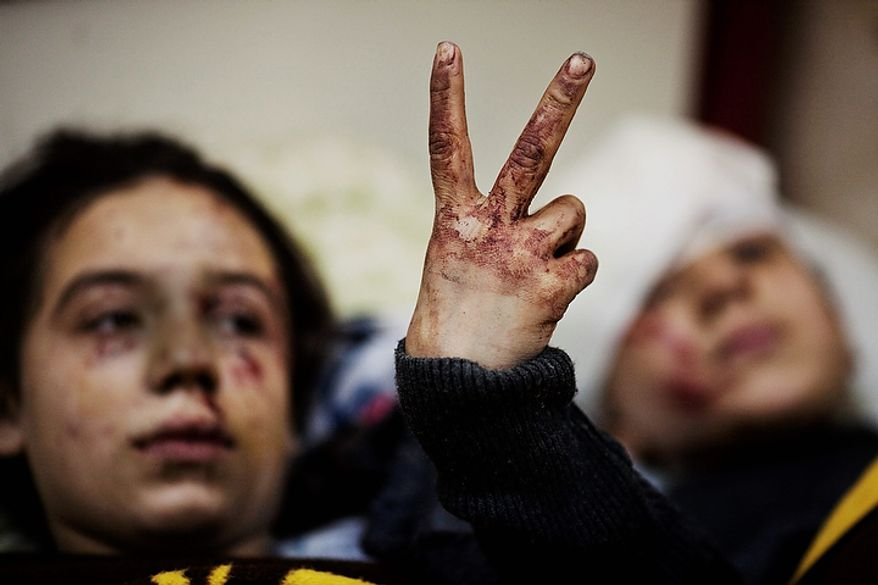 In this photo from March 10, 2012, Hana, 12, flashes the victory sign next to her sister Eva, 13, as they recover from severe injuries after the Syrian Army shelled their house in Idlib, north Syria. Their father and two siblings were killed. (Associated Press)