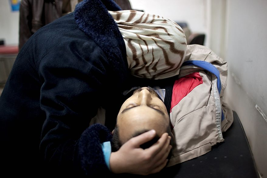 In this photo from March 11, 2012, the wife of Mohammed Halak mourns after the man was killed by gunfire during fierce fighting between the Free Syrian Army and the government forces in Idlib, north Syria. (Associated Press)