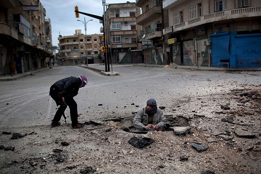 In this photo from March 11, 2012, Free Syrian Army fighters plant a roadside bomb to destroy a Syrian Army tank during a day of fierce fighting with the government forces in Idlib, north Syria. (Associated Press)