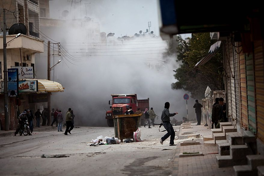 In this photo from March 11, 2012, Free Syrian Army fighters are seen amid smoke from tank shelling during a day of fierce fighting with the government forces in Idlib, north Syria. At least four rebels were killed and several were injured when the tank shell landed. (Associated Press)