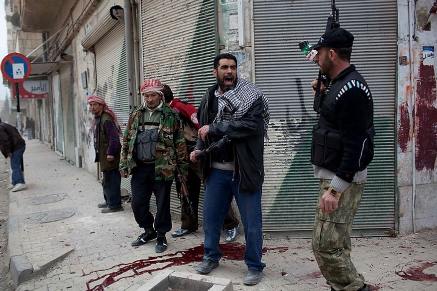 In this photo from March 11, 2012, a Free Syrian Army fighter calls for reinforcements as they take cover on a corner in Idlib, north Syria. (Associated Press)