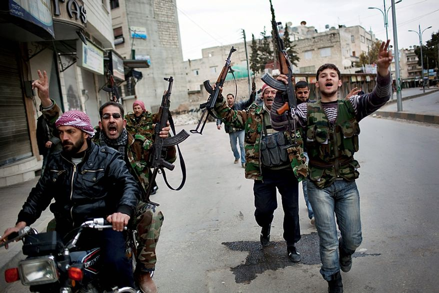 In this photo from March 11, 2012, Free Syrian Army fighters celebrate after hearing that their comrades destroyed a Syrian Army tank in Idlib, north Syria. (Associated Press)