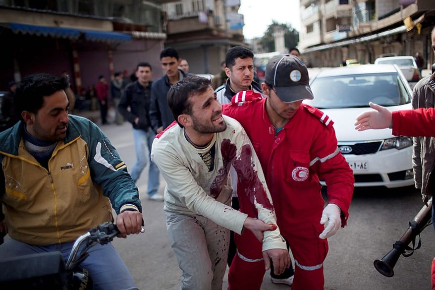 In this photo from March 11, 2012, medics help a wounded man outside a hospital during fighting between Syrian rebels and government forces in Idlib, north Syria. Scores of people have been reported dead during clashes between Government forces and Free Syrian Army fighters. (Associated Press)