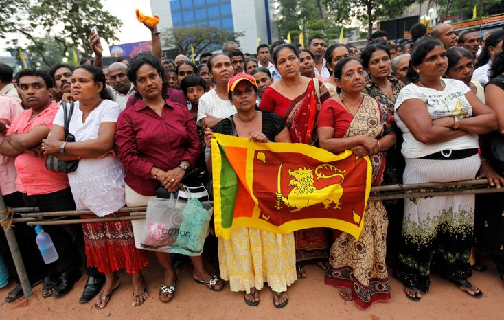 Government supporters hold a national flag during a rally against an American-backed proposed U.N. Human Rights Council resolution on alleged human rights abuses during the country's civil war, in Colombo, Sri Lanka, on Tuesday. (Associated Press)