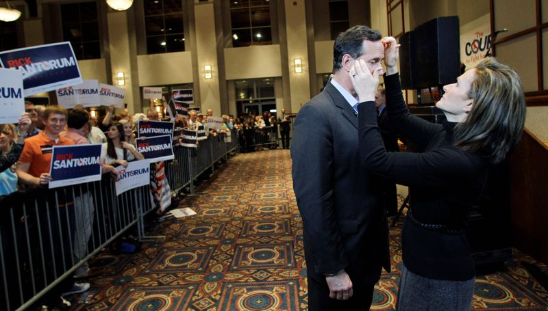 Karen Santorum helps prepare her husband, Republican presidential hopeful Rick Santorum, for an interview after a rally Monday in Montgomery, Ala. Mr. Santorum is putting up a fight against his well-funded rival, Mitt Romney. (Associated Press)