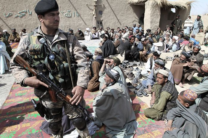 An Afghan security guard keeps watch Tuesday as villagers listen to a speech by an Afghan official. They are part of a delegation attending a prayer ceremony for civilian victims in a killing spree Sunday, possibly by a U.S. soldier, in Kandahar province. (As