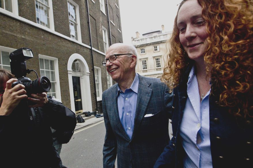 ** FILE ** News Corp. Chairman Rupert Murdoch (center) and Rebekah Brooks, then the chief executive of News International, leave Mr. Murdoch's residence in central London on Sunday, July 10, 2011. (AP Photo/Sang Tan, File)