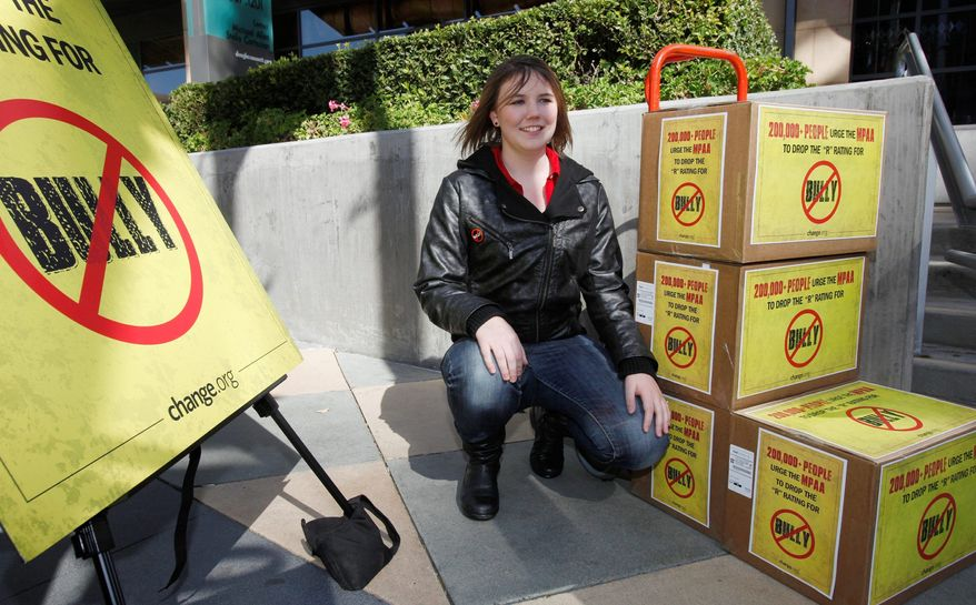 "Katy Butler, 17, a high school student, from Ann Arbor, Mich., poses by the petitions she delivered to the Motion Picture Association of America, Wednesday March 7, 2012, in Los Angeles. Butler is urging the MPAA to change the ""R"" rating to a ""PG"" for the ""Bully"" film. With her petition, Butler said that she was speaking out for all students who suffer every day from bullying. (AP Photo/Damian Dovarganes)"