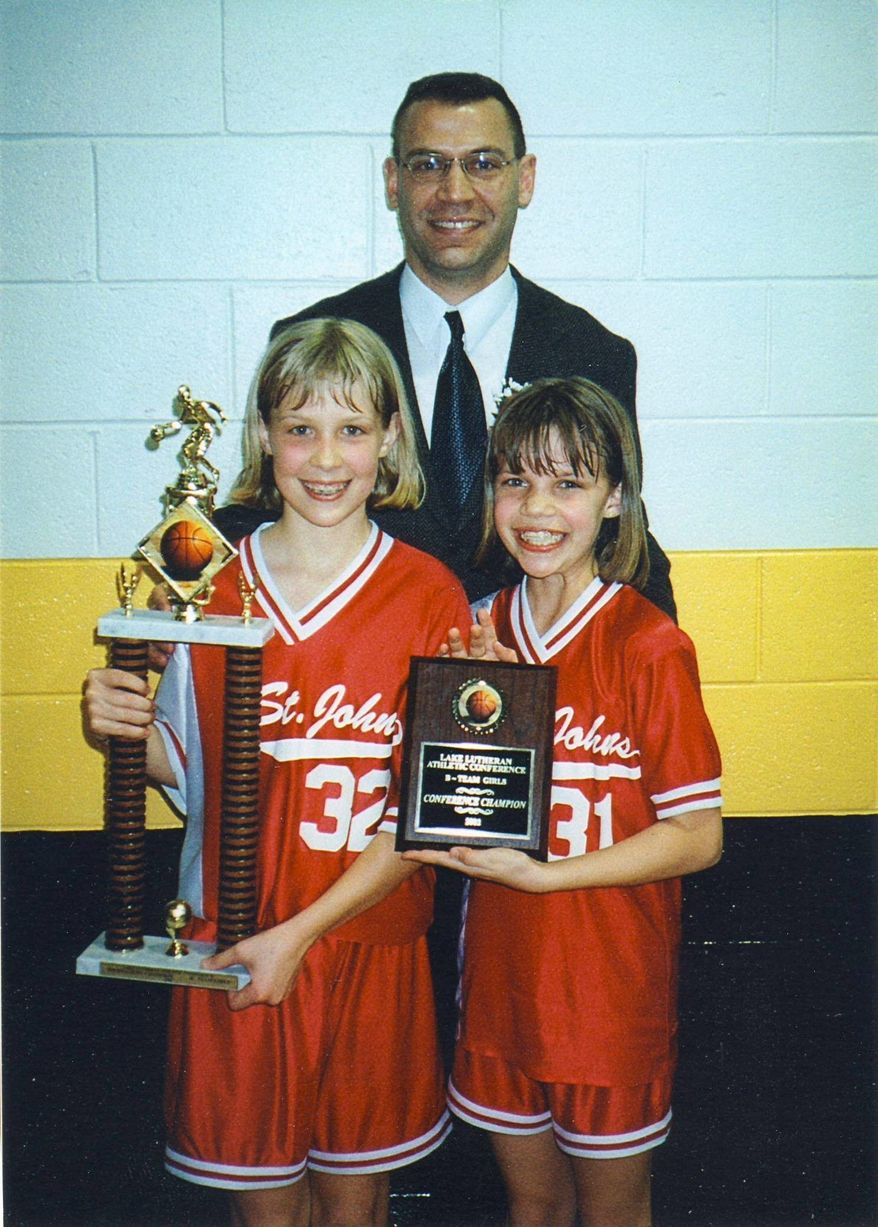 Lydia Bauer holds a trophy and her sister, Audrey, holds a plaque after winning a tournament with their grade-school team at St. John's Lutheran School in Libertyville, Ill., coached by dad Andrew Bauer. Their mom was a high school coach. (Bauer family)