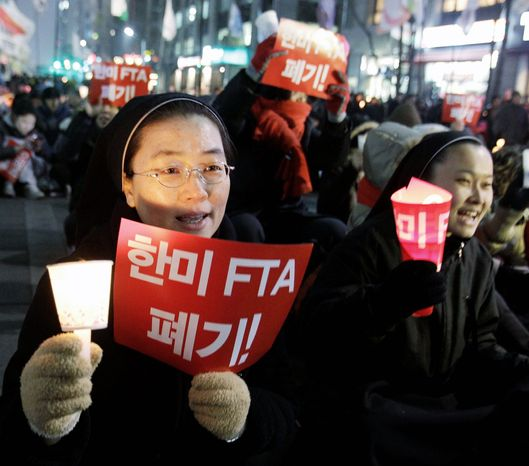 Nuns were among the protesters at a South Korean rally against the trade pact, which went into effect at midnight Wednesday. (Associated Press)