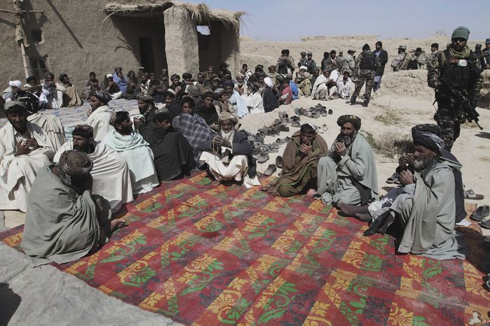 Afghan villagers pray during a ceremony on Tuesday, March 13, 2012, for the victims of Sunday's killing of 16 civilians allegedly by a U.S. soldier in Panjwai, Afghanistan. (AP Photo/Allauddin Khan)