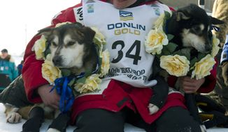 Dallas Seavey holds his lead dogs, Diesel (left) and Guinness, after claiming victory in the Iditarod Trail Sled Dog Race in Nome, Alaska, on Tuesday, March 13, 2012. Seavey is the youngest musher to win the nearly 1,000-mile race across Alaska. (AP Photo/Marc Lester, Anchorage Daily News)