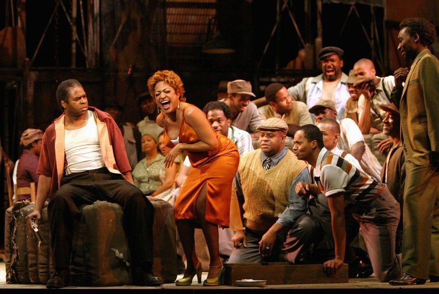 """Terry Cook as the murderous, possessive Crown (seated) and Indira Mahajan as Bess rehearse for Washington National Opera's recent production of """"Porgy and Bess."""" (Washington National Opera via Associated Press)"""