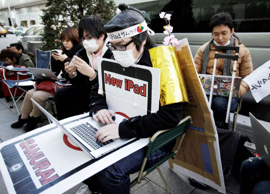 Ryo Takahashi wearing a samurai wig browses internet as he and others wait in a queue to buy a new iPad outside an Apple Store in Tokyo, Thursday, March 15, 2012, one day before the the new iPad goes on sale Friday. (AP Photo/Shizuo Kambayashi)