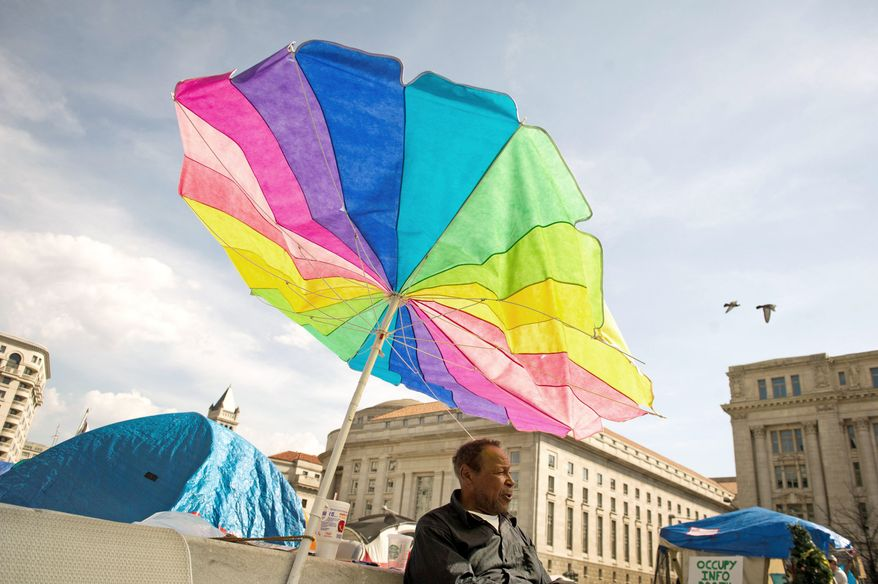 As temperatures reached an unusual high, Washington, D.C. native James Fisher, 70, seeks shelter from the sun behind a colorful umbrella at the Occupy DC encampment he has called home since October of 2011 at Freedom Plaza in Washington, D.C., Thursday, March 15, 2012. (Rod Lamkey Jr./The Washington Times)