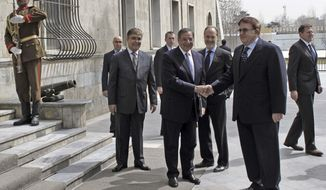 U.S. Defense Secretary Leon E. Panetta (center) shakes hands with his Afghan counterpart, Abdul Rahim Wardak, on Thursday, March 15, 2012, in Kabul, Afghanistan. (AP Photo/Mohammad Ismail, Pool)