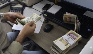 ** FILE ** A currency exchange bureau worker counts U.S. dollars, as Iranian bank notes are seen at right with portrait of late revolutionary founder Ayatollah Khomeini, in downtown Tehran, Iran, in this Wednesday, Dec. 21, 2011, file photo. (AP Photo/Vahid Salemi, file)