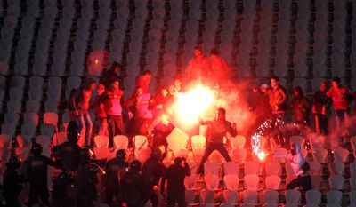 **FILE** Egyptian fans clash with riot police on Feb. 1, 2012, following the Al-Ahly club soccer match against the Al-Masry club at the soccer stadium in Port Said, Egypt. (Associated Press)