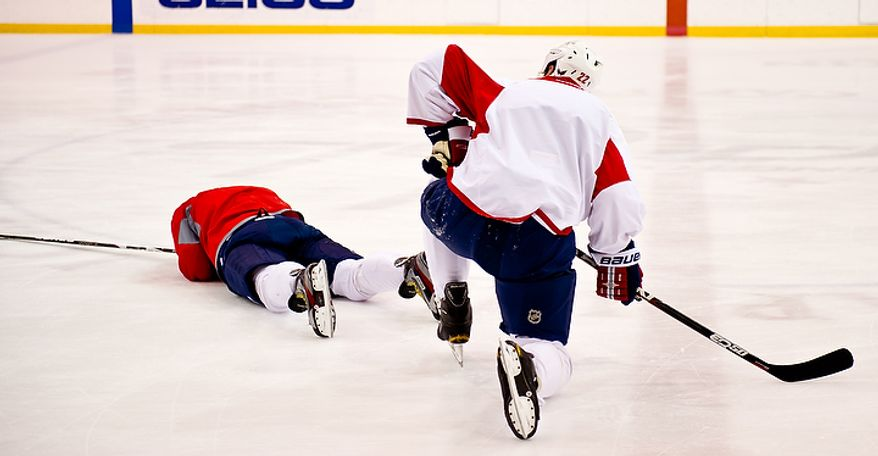 Washington Capitals left wing Alex Ovechkin (8) lays on the ice after a center ice collision with Washington Capitals right wing Mike Knuble (22), right, during a morning practice at Kettler Capitals Iceplex, Arlington, Va., March 15, 2012. Ovechkin stayed on the ice for two minutes and then sat on the bench for another three and a half minutes before leaving practice. Knuble appeared to be ok. (Andrew Harnik/The Washington Times)