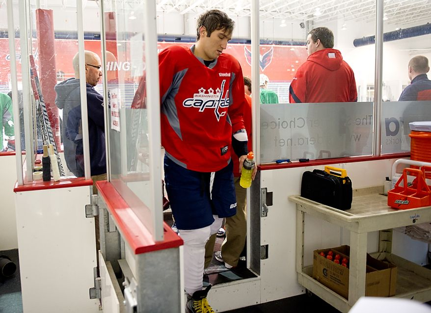 Teammates surround Washington Capitals left wing Alex Ovechkin (8) leaves practice after a center ice collision with Washington Capitals right wing Mike Knuble (22) during a morning practice at Kettler Capitals Iceplex, Arlington, Va., March 15, 2012. Ovechkin stayed on the ice for two minutes and then sat on the bench for another three and a half minutes before leaving practice. (Andrew Harnik/The Washington Times)