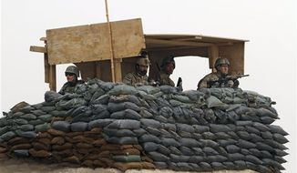 FILE - In this Sunday, March 11, 2012 file photo, U.S. Army and Afghan soldiers are seen in a guard tower at their base in Panjwai, Kandahar province south of Kabul, Afghanistan, following the alleged killing of 16 civilians by a U.S. soldier. U.S. investigators have determined that the suspect had been drinking alcohol prior to leaving the base the night of the attack, a senior U.S. defense official said Friday. How much of a role alcohol played in the attack is still under investigation, said the official, speaking on condition of anonymity because charges have not yet been filed. (AP Photo/Allauddin Khan, File)