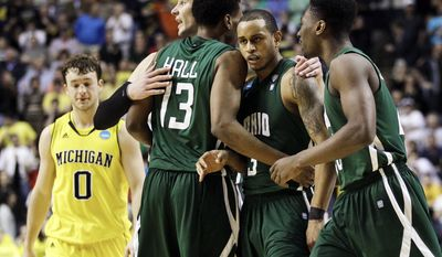 Ohio guard Walter Offutt, second from right, is congratulated by Ivo Baltic, fourth from right, T. J. Hall (13) and Ricardo Johnson, right, after Offutt drew a foul against Michigan in the final seconds of a second-round NCAA college basketball tournament game on Friday, March 16, 2012, in Nashville, Tenn. The resulting free throws by Offutt sealed a 65-60 win for Ohio. (AP Photo/Mark Humphrey)