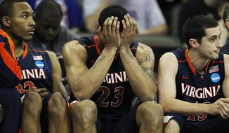 Virginia forward Mike Scott (23) holds his head while on the bench with teammates Darion Atkins (32) and Sammy Zeglinski (13) during the second half of a tournament game against Florida at CenturyLink Center in Omaha, Neb., Friday, March 16, 2012. Florida defeated Virginia 71-45. (AP Photo/Orlin Wagner)