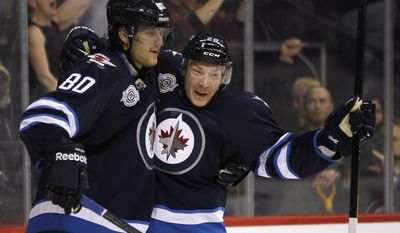 Winnipeg Jets' Nik Antropov (80) and Antti Miettinen (20) celebrate Antropov's goal against the Washington Capitals during the second period of an NHL hockey game in Winnipeg, Manitoba, on Friday, March 16, 2012. (AP Photo/The Canadian Press, John Woods)