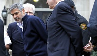 Actor George Clooney (center); Rep. James P. Moran (back), Virginia Democrat; and Mr. Clooney's father, Nick Clooney (right), are arrested on Friday, March 16, 2012, during a protest at the Sudanese Embassy in Washington. The demonstrators were protesting the escalating humanitarian emergency in Sudan that threatens the lives of 500,000 people. (Associated Press)