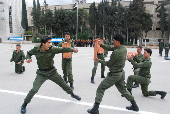 In this photo released by the Syrian official news agency SANA, Syrian police officers demonstrate their skills March 15, 2012, during the graduation of instructor officers on fighting techniques under the supervision of North Korean experts at Bassel Assad police academy in Damascus, Syria. (Associated Press/SANA)