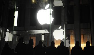 ** FILE ** People gather March 16, 2012, outside an Apple retail store on Fifth Avenue in the Manhattan borough of New York as they wait for the 8 a.m. release of the new iPad tablet. (Associated Press)