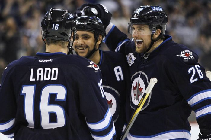 Winnipeg Jets' Andrew Ladd (16), Dustin Byfuglien (33) and Blake Wheeler (26) celebrate Byfuglien's goal against the Dallas Stars during the second period in Winnipeg, Manitoba, on Wednesday, March 14, 2012. (AP Photo/The Canadian Press, John Woods)