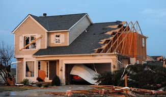 A house is missing part of its roof on Noble Drive in Huron Farms neighborhood of Dexter, Mich., on March 15, 2012, after a tornado hit the neighborhood. The slow-moving storm was part of a system packing large hail, heavy rain and high winds. (Associated Press/AnnAbor.Com)