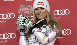 Lindsey Vonnshows her trophy for winning the alpine ski women's World Cup super-combined discipline title in Schladming, Austria, Saturday, March 17, 2012. (AP Photo/Armando Trovati)