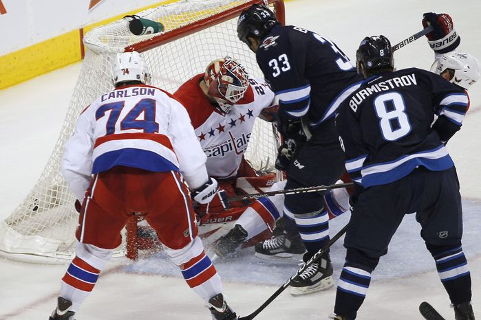 Winnipeg Jets' Dustin Byfuglien (33) scores the game-winning goal in the third period against the Washington Capitals in Winnipeg, Manitoba, on Friday, March 16, 2012. (AP Photo/The Canadian Press, John Woods)