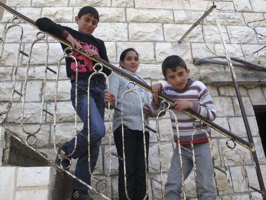 ** FILE ** In this March 12, 2012, photograph, Mahmoud al-Alami, 10, left, stands in front of his home with his cousin Farah, center, and brother Mamoun in Beit Umar, West Bank. (AP Photo/Diaa Hadid)
