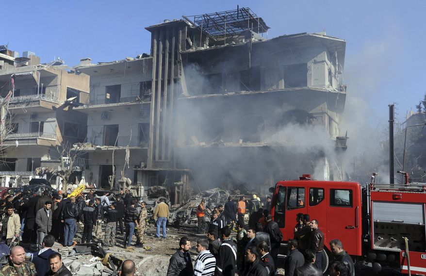 In this photo released by the Syrian official news agency SANA, Syrian security forces gather in front of a damaged building near the aviation intelligence department, which was attacked by one of two explosions, in Damascus, Syria, on Saturday, March 17, 2012. (AP Photo/SANA)