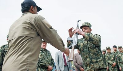 ASSOCIATED PRESS A former private security guard (left) hands over his weapon to Jamal Abdul Naser Sidiqi, head of the Afghan Public Protection Force, during a transition ceremony Thursday of private security forces to Afghan Public Protection Force on the outskirts of Kabul. The Afghan government is giving companies extensions ranging from a few weeks to 90 days.
