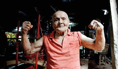 Manohar Aich flexes his muscles on Friday in a gymnasium in Kolkata. Mr. Aich, who is 4 feet 11 inches tall, won the Mr. Universe title in London in 1952. Happiness and a life without tensions are the key to his longevity, said Mr. Aich, who turned 100 on Saturday. (Associated Press)