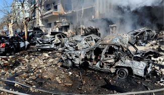 Destroyed cars on Sunday litter the area near the Syrian aviation intelligence department in Damascus. Bombs struck government targets in the Syrian capital early Saturday, killing security forces and civilians and leaving pools of blood and carnage in the streets, according to state-run television. (Associated Press)