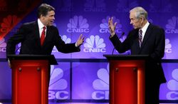 Texas Gov. Rick Perry and Rep. Ron Paul, of Texas, go head to head during the Republican presidential debate at Oakland University in Auburn Hills, Mich., on Nov. 9, 2011. (Associated Press)