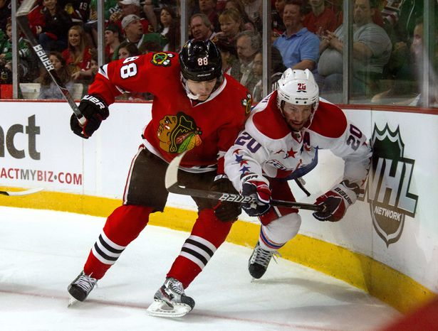Chicago Blackhawks' Patrick Kane checks Washington Capitals' Troy Brouwer during the first period of an NHL hockey game in Chicago on Sunday, March 18, 2012. (AP Photo/Charles Cherney)