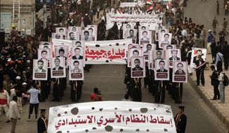 """Demonstrators hold pictures of slain protesters as they march in Sanaa, Yemen, on Sunday, March 18, 2012, to commemorate those who were killed a year ago in a particularly bloody protest. The writing in Arabic on the banner (foreground) reads, """"Overthrow the family dictatorial regime."""" (AP Photo/Hani Mohammed)"""