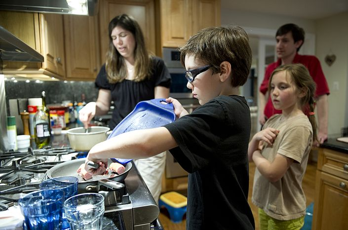 Eleven-year-old Forrest Johnston helps his mom Jill prepare dinner at their Great Falls, Va., home on Thursday, March 15, 2012 while sister Beth, 9, and dad Rich look on. (Barbara L. Salisbury/The Washington Times)