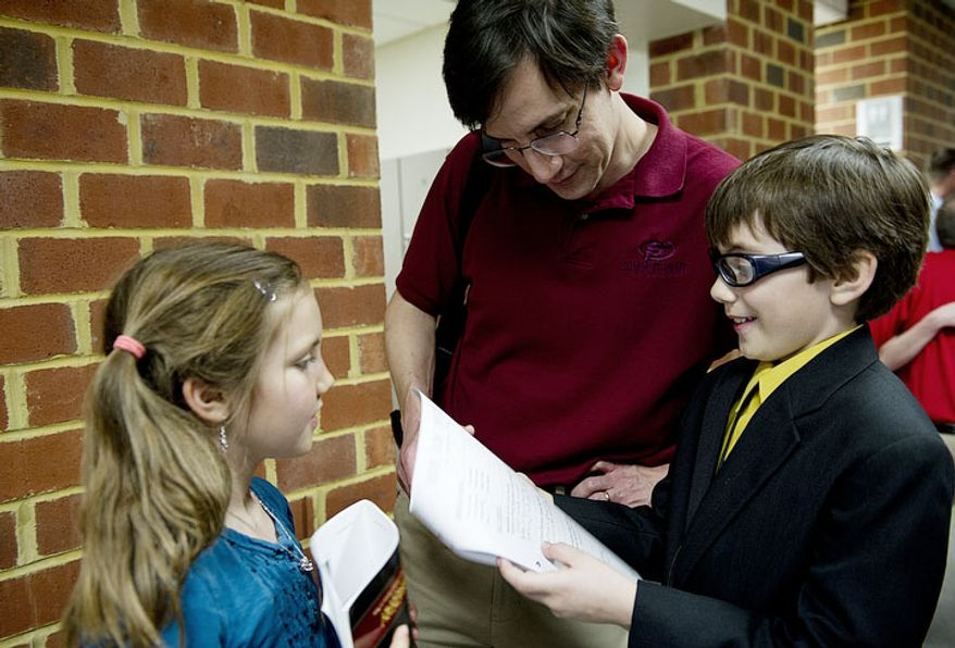 While his sister Beth, 9, left, looks on, Forrest Johnston, 11, goes through the judges' comments with his dad Rich following his performance at the National Trumpet Competition. The students are able to get a sense of what the judges thought of their performances even before the results are announced. (Barbara  L. Salisbury/The Washington Times)