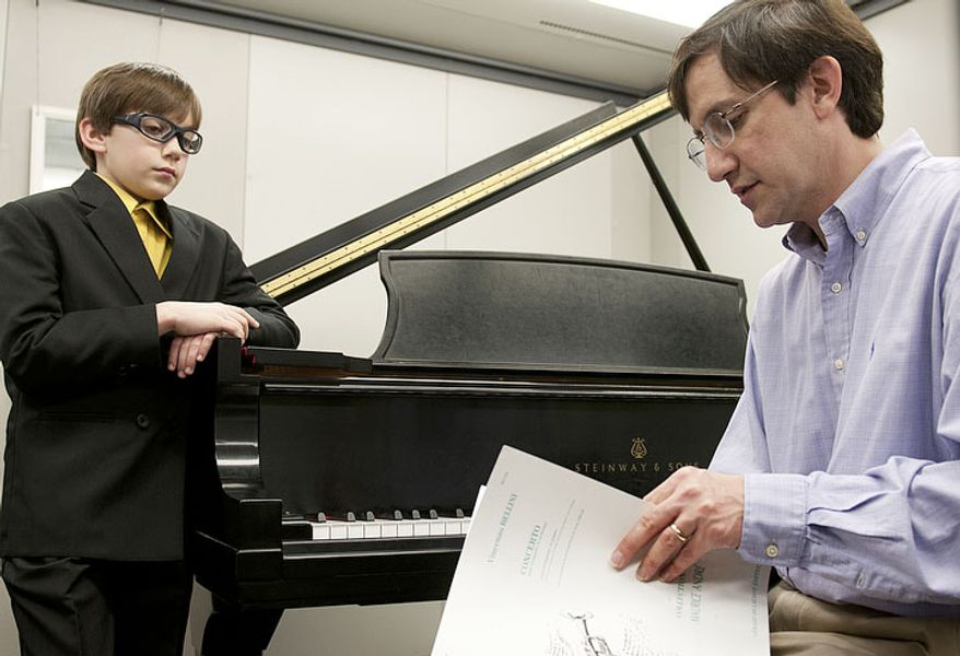 Forrest and his dad Rich Johnston go over some last-minute details in one of the practice rooms at George Mason University before Forrest performing in the finals of the National Trumpet Competition on Sunday, March 18, 2012. Forrest, 11, was one of only three competitors in the Junior division to make it through to the final round. He was the youngest competitor. (Barbara L. Salisbury/The Washington Times)